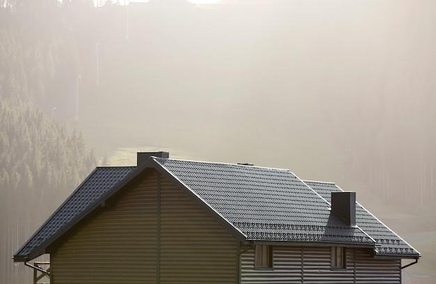 Techo de la cabaña con paredes de revestimiento, techo de tejas marrones y altas chimeneas en el área ecológica en un paisaje de niebla