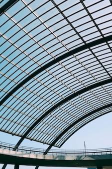 Techo de cristal de un edificio moderno bajo el cielo azul