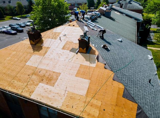 El techo repara el reemplazo del techo viejo con tejas nuevas de un apartamento
