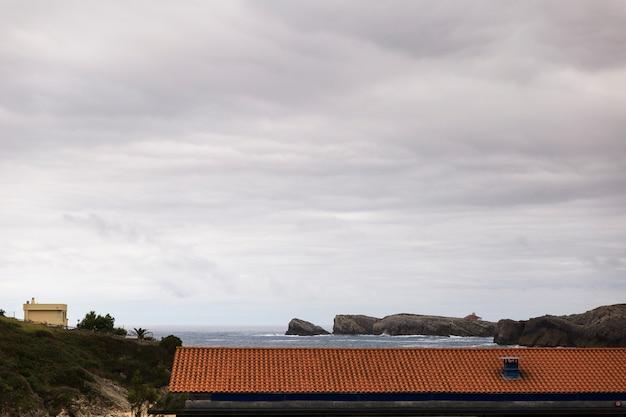 Techo rojo de casa en la costa
