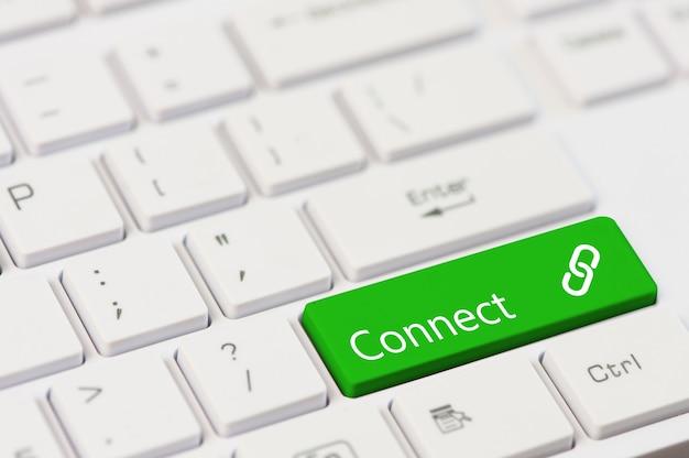 Una tecla verde con texto conectar en el teclado de un portátil blanco.