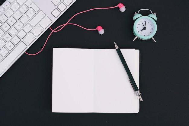 Teclado y auriculares cerca de notebook y reloj despertador