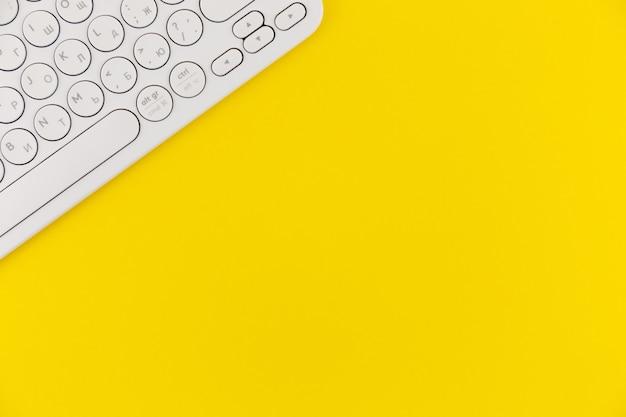 Teclado blanco sobre fondo amarillo espacio vacío para texto