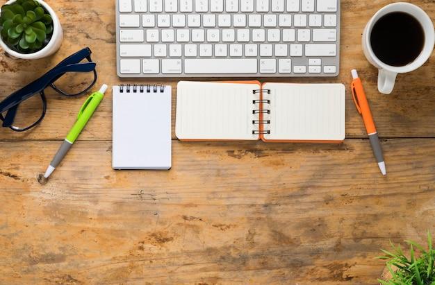 Teclado; bloc de notas espiral taza de café; anteojos y pluma en escritorio de madera