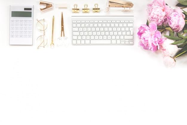 Teclado, bolígrafo dorado, gafas, calculadora y un ramo de peonías rosas sobre un fondo blanco. copie el espacio.