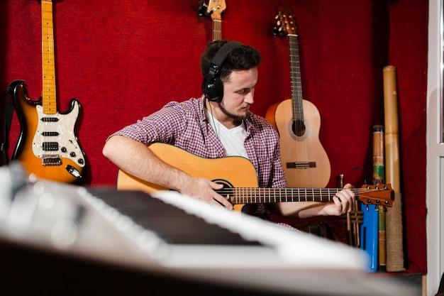 Teclado borroso y chico tocando la guitarra