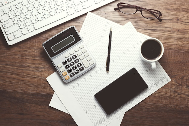 Teclado, calculadora y útiles de oficina en la mesa.