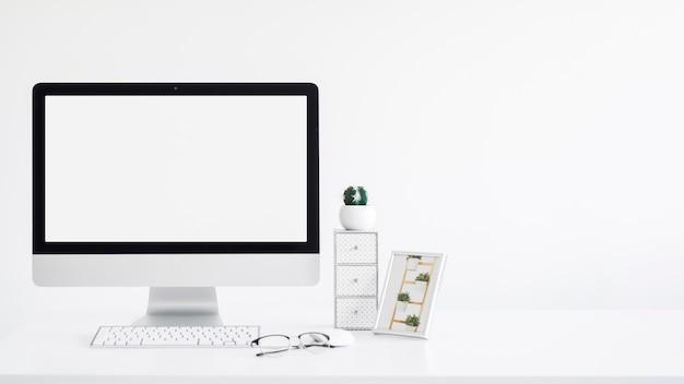 Teclado cerca del monitor, marco de fotos, cactus y anteojos en mesa