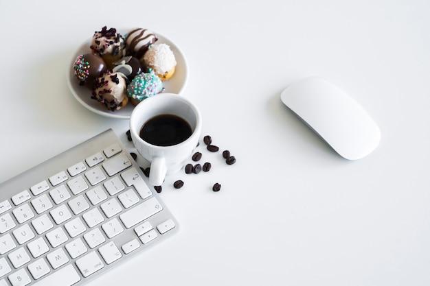Teclado cerca de taza, galletas y ratón de ordenador.