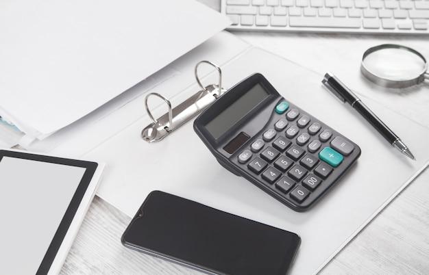 Teclado de computadora, bolígrafo, calculadora, documento en el escritorio
