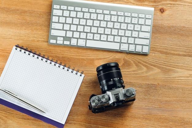 Teclado de computadora, bolígrafo, cámara y bloc de notas