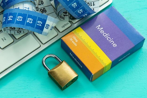 Teclado de computadora con cinta métrica y caja de medicamentos junto a un candado cerrado
