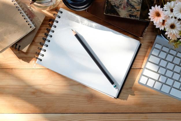 El teclado de computadora del escritorio de oficina, el café, la flor, el cuaderno en la tabla de madera y la mañana se encienden con la visión superior.