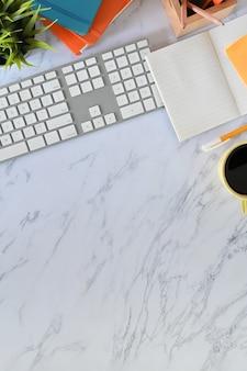 Teclado de computadora de escritorio de oficina, café, portalápices, cuaderno y planta con mesa de vista superior.