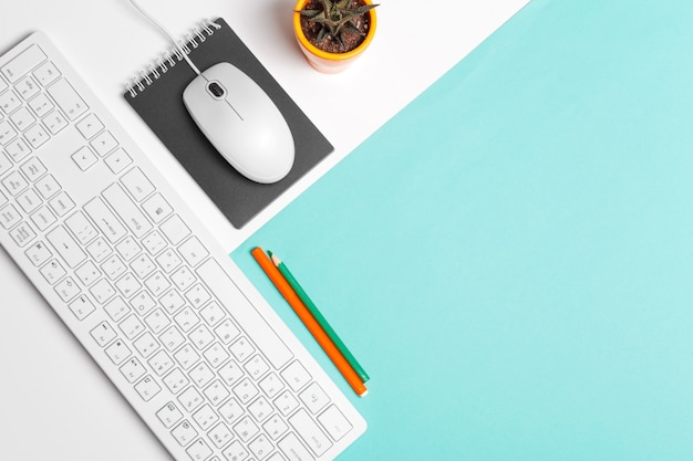 Teclado de computadora y mouse sobre fondo de bloque de color, interior de oficina