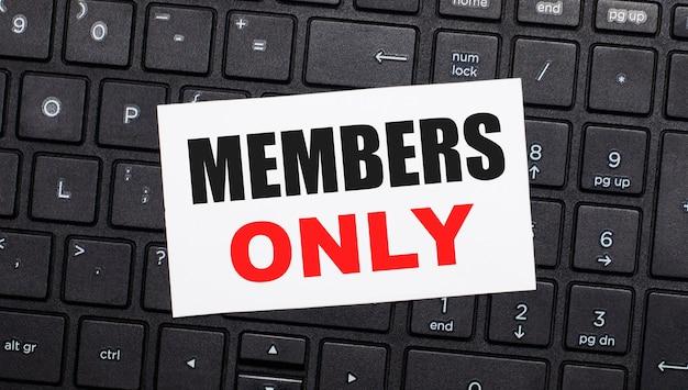 En un teclado de computadora negro hay una tarjeta blanca con el texto solo miembros. vista desde arriba
