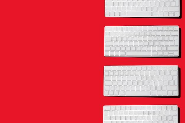 Teclado de una computadora sobre un fondo rojo