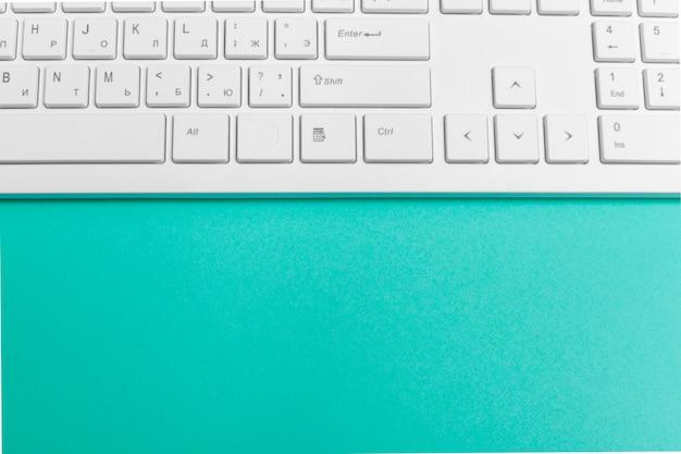 Teclado de computadora sobre papel turquesa