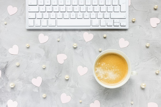 Teclado de computadora, taza de café, corazones de color rosa, perlas blancas en el escritorio de la mujer, fondo gris. preparación del día de las vanetinas, estilo de vida, compras por internet, concepto de sitios de citas en línea. lay flat, espacio de copia