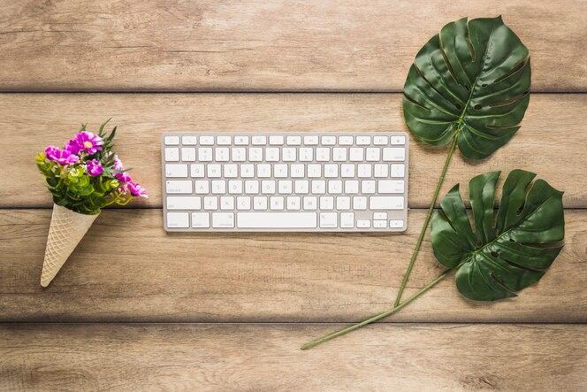 Teclado de computadora con hojas y flores