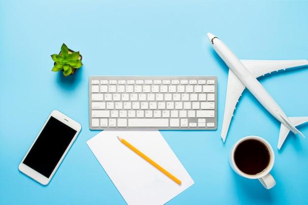Teclado, flor, avión, taza con té o café, una hoja en blanco y un lápiz sobre un azul