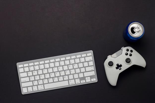 Teclado, gamepad y una lata de bebida sobre un fondo negro. el concepto del juego en la pc, juegos, consola. vista plana, vista superior.