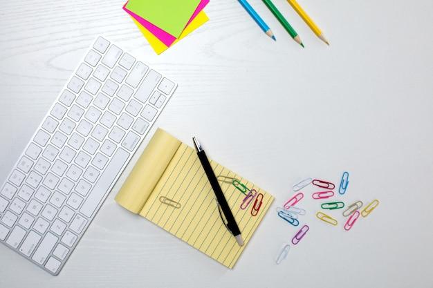 Teclado inalámbrico y bloc de notas amarillo sobre la mesa