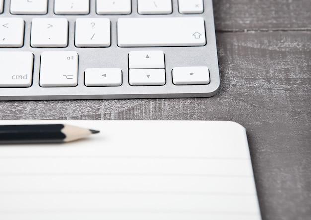 Teclado con lápiz en cuaderno abierto en escritorio de oficina
