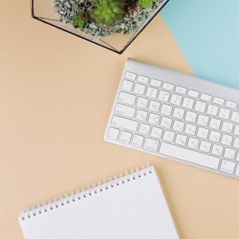 Teclado con libreta y planta sobre mesa