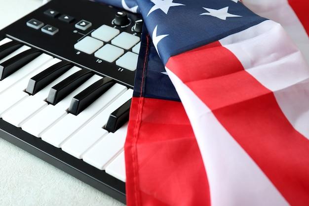 Teclado midi y bandera americana sobre fondo blanco con textura