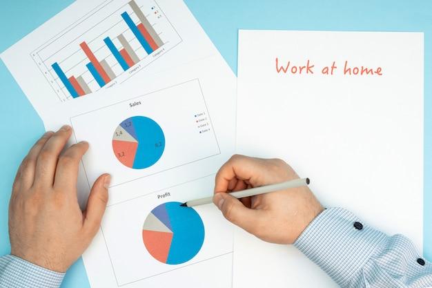 Teclado y mouse blancos. el hombre de la mesa trabaja con documentos y gráficos. trabajo remoto, autoaislamiento, trabajo en casa, cuarentena.