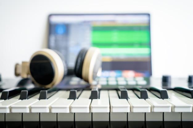 Teclado de música y auriculares de mezcla de música en la estación de música de la computadora