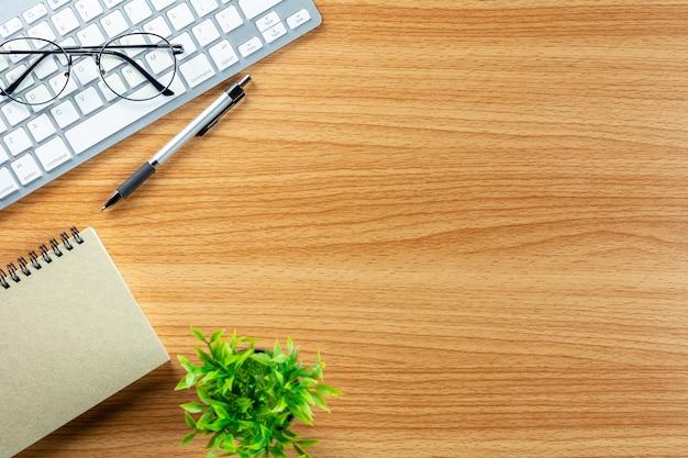 Teclado de ordenador, pluma, cuaderno y gafas en el escritorio de madera.