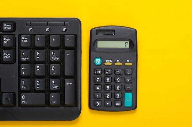 Teclado de pc y calculadora en amarillo. espacio de trabajo