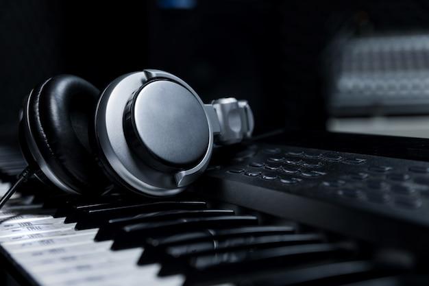 Teclado de piano con auriculares para música, auriculares con teclado de piano, primer plano, auriculares con fondo de piano eléctrico por el fondo de instrumentos musicales.