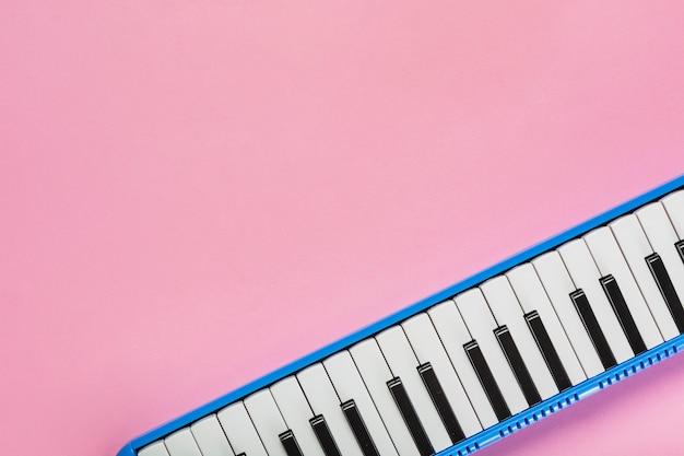 Teclado de piano blanco y negro sobre fondo rosa