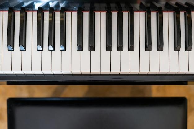 Teclado de piano clásico con asiento.
