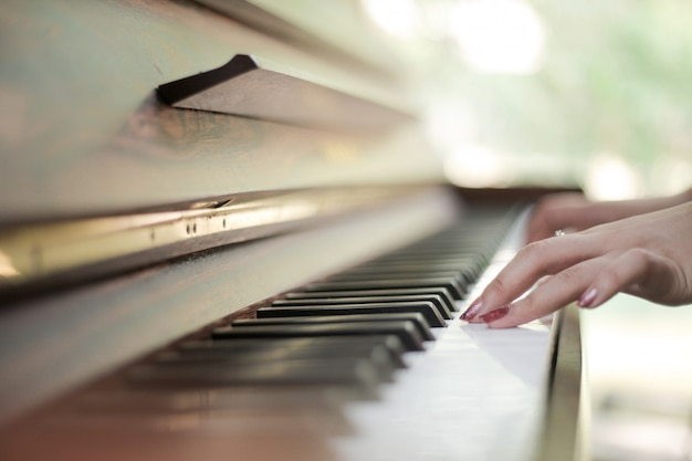 Teclado de piano con manos femeninas jugando en él