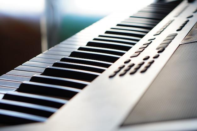 Teclado de piano sintetizador electrónico en la macro de los rayos del sol. rayos de luz de colores de alta tecnología.