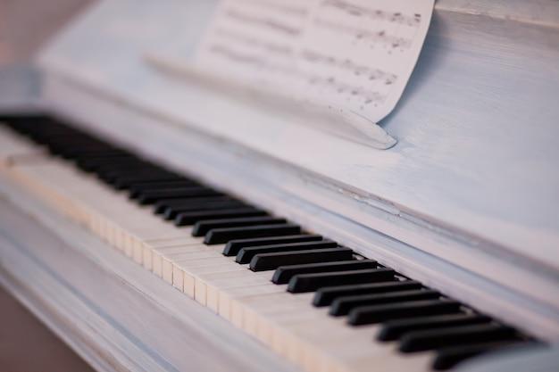 Teclado de piano vintage blanco con tecla en blanco y negro y partituras.