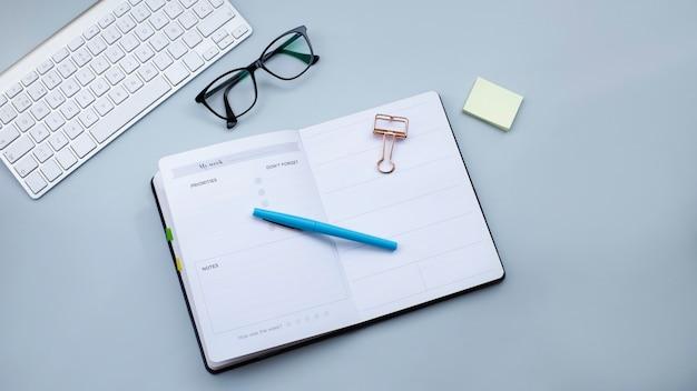 Teclado de planificador abierto y gafas sobre una superficie gris clara los impuestos a las pequeñas empresas funcionan concepto imagen de banner web
