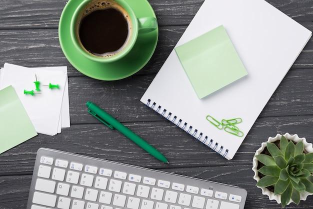 Teclado con planta suculenta y notas adhesivas sobre escritorio de madera