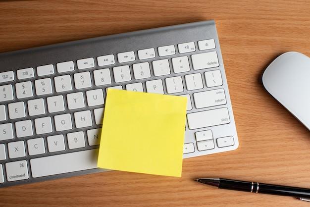 Teclado y ratón con libretas amarillas y bolígrafo negro.