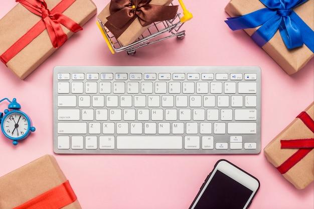 Teclado, reloj despertador, teléfono móvil y cajas de regalo dispuestas alrededor del teclado sobre una superficie rosa. concepto de ordenar y comprar regalos en internet, tienda en línea. vista plana, vista superior.