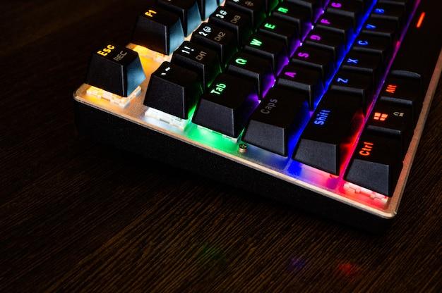 Teclado rgb mecánico de juegos profesionales multicolores sobre la mesa