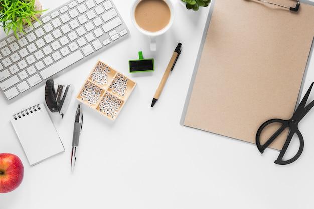 Teclado con suministros de oficina; té y manzana sobre fondo blanco