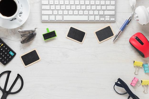Teclado; tarjetas en blanco; taza de café y suministros de oficina en el escritorio