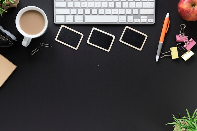Teclado; taza de té papelería de oficina y manzana sobre fondo negro