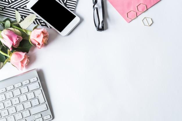 Teclado, un teléfono inteligente, gafas y rosas rosadas sobre una superficie blanca