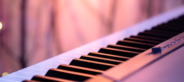 Teclas de música bajo iluminación de colores sobre un fondo borroso.